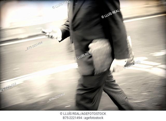 Closeup of an unrecognizable executive walking down the street with documents in hand, City of London, England, UK