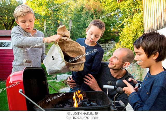 Mid adult man and sons preparing barbecue in garden