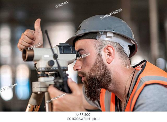 Young male surveyor looking through theodolite giving thumbs up on construction site