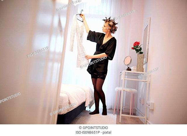 Woman with hair rollers choosing dress