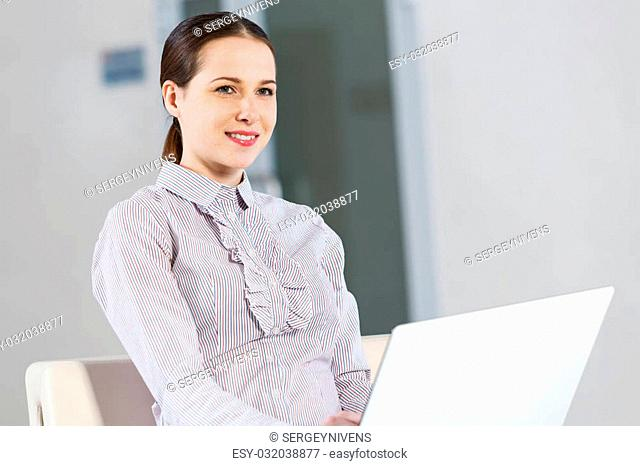 Young pretty girl in casual sitting and using laptop