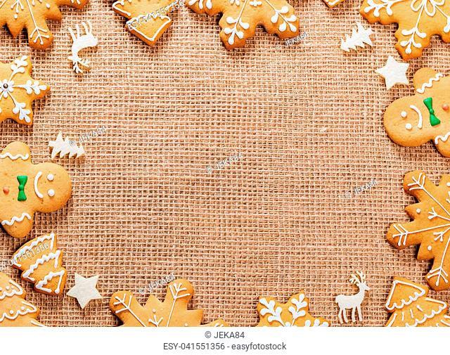 Christmas gingerbread cookies homemade and New Year decor on table with burlap tablecloth. Merry Christmas postcard. Frame with free space