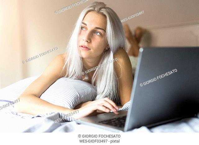 Young woman lying in bed using laptop