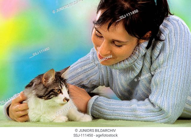 young woman fondling a Norwegian Forest Cat