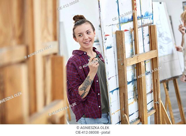Female artist painting at easel in art class studio