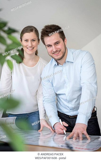 Smiling young man and woman in office with calendar