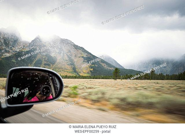 USA, Wyoming, Grand Teton National Park, wing mirror with mirror image of woman taking picture