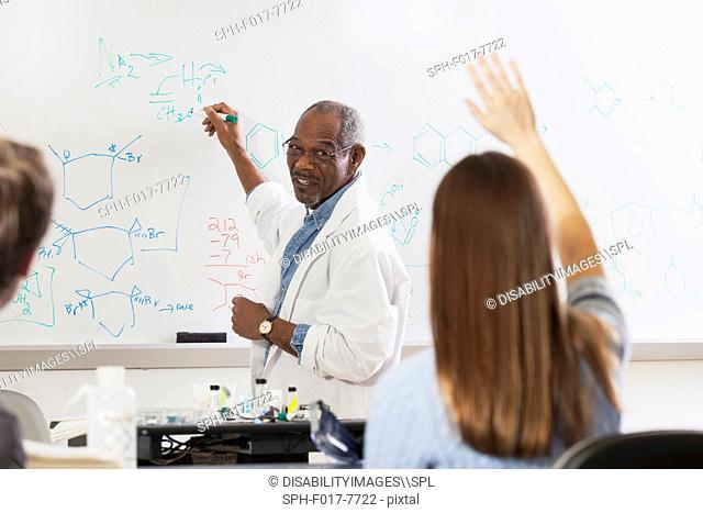 Student raising her hand in an engineering class while professor is at the white board writing about chemical bonds