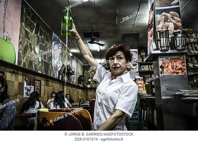 Waitress pouring Cider from a height, the most tipycal alcoholic beverage in Gijon, Asturias