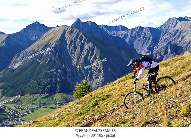 Italy, Livigno, View of man riding mountain bike downhill
