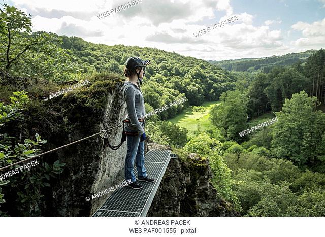 Germany, Westerwald, Hoelderstein, woman on via ferrata looking at view
