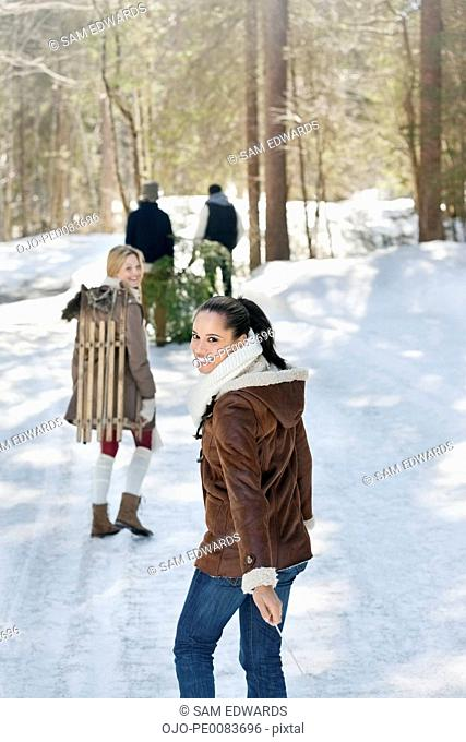 Smiling friends with fresh cut Christmas tree and sled in snowy woods