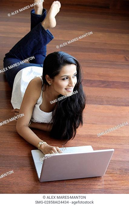 young woman on floor, using laptop
