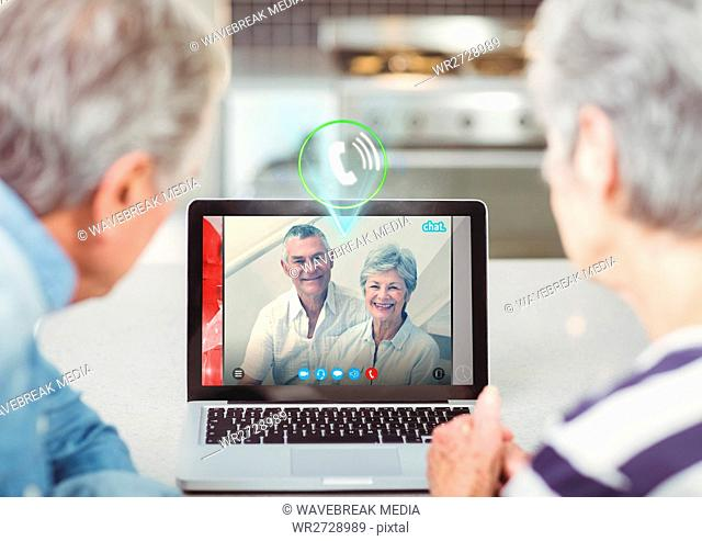 Senior couple having video call with friends on laptop