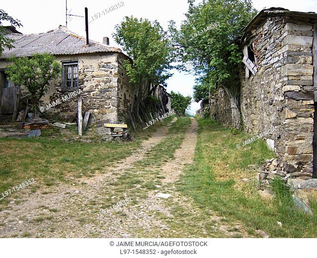 Gravel road between two stone buildings in the village of Foncebadon along the Camino de Santiago
