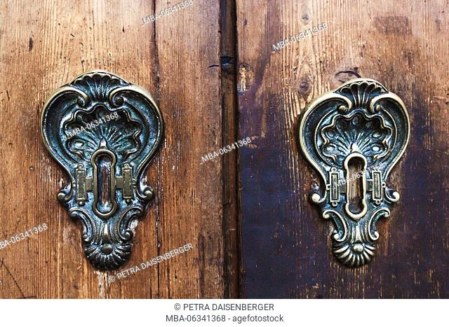 Two antique, forged locks in a wooden door, a detailed view