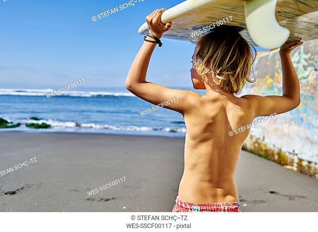 Chile, Pichilemu, boy carrying surfboard at the sea