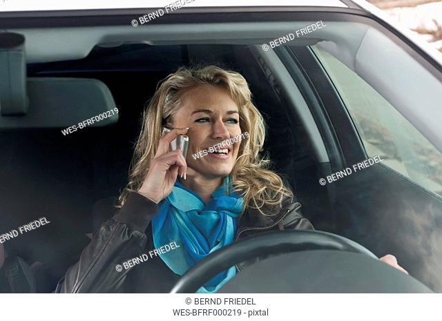 Germany, Brandenburg, Woman talking on mobile phone in car