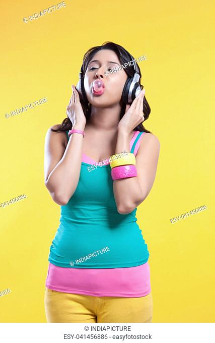 Woman blowing bubble while listening to music