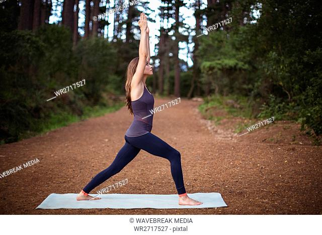 Woman performing yoga on exercise mat