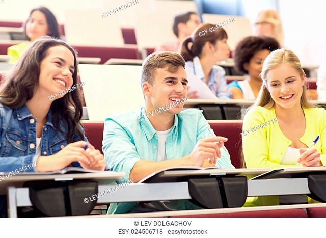 education, high school, university, learning and people concept - group of international students with notebooks in lecture hall