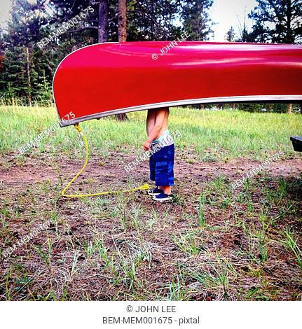 Caucasian boy carrying canoe in field
