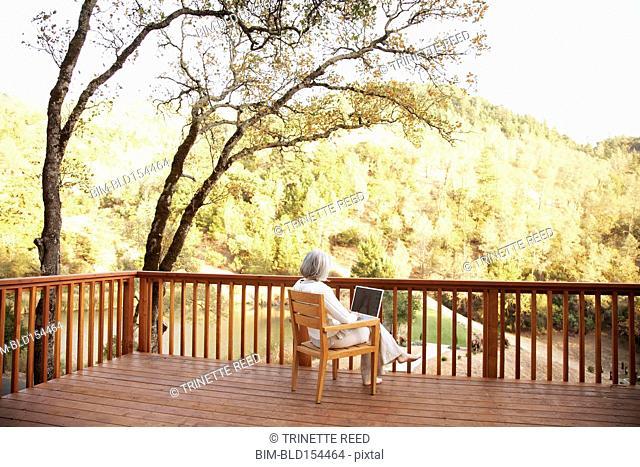 Older Caucasian woman using laptop on wooden deck