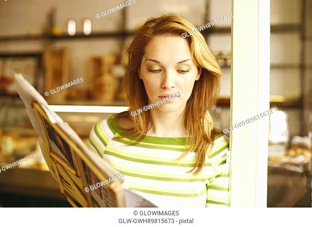 Close-up of a young woman reading a menu card