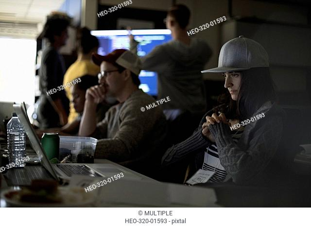 Focused female hacker wearing baseball cap working hackathon at laptop in dark office