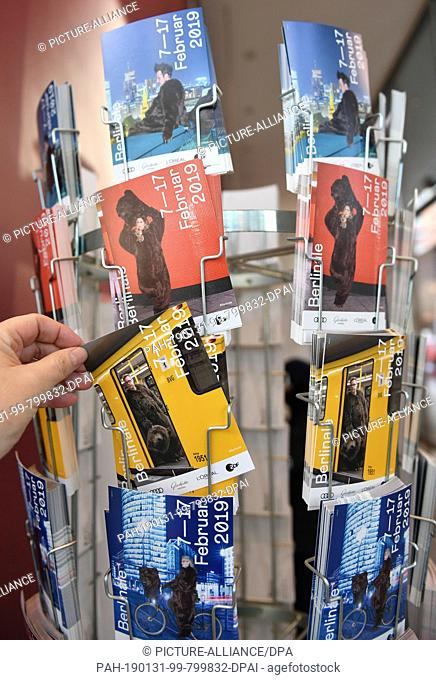 31 January 2019, Berlin: A man at Potsdamer Platz reaches for information material from the International Film Festival. The Berlinale takes place from 07 to 17...