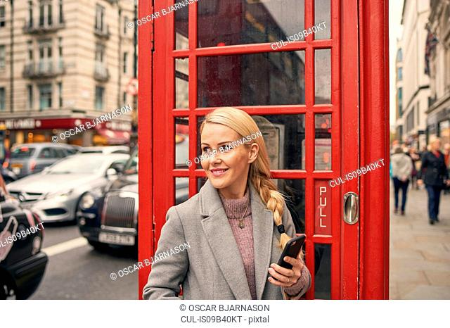 Mid adult woman standing in front of telephone box, holding smartphone