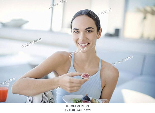 Portrait smiling, confident brunette woman eating figs