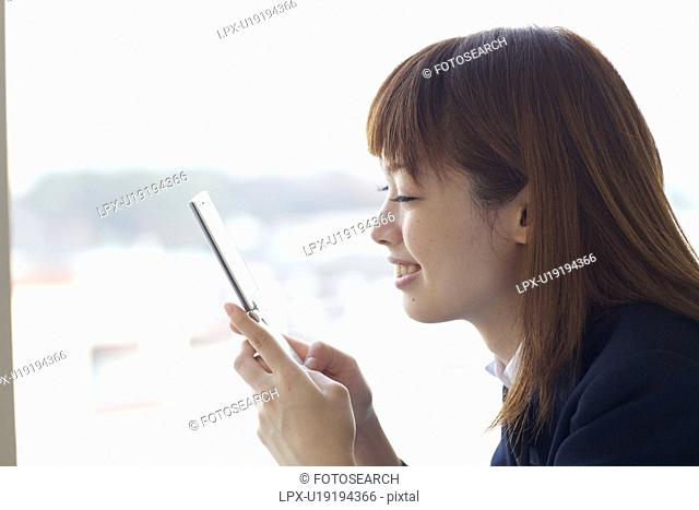 High School Student Looking at Mobile Phone
