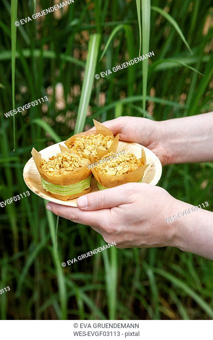 Person holding plate with oat muffins
