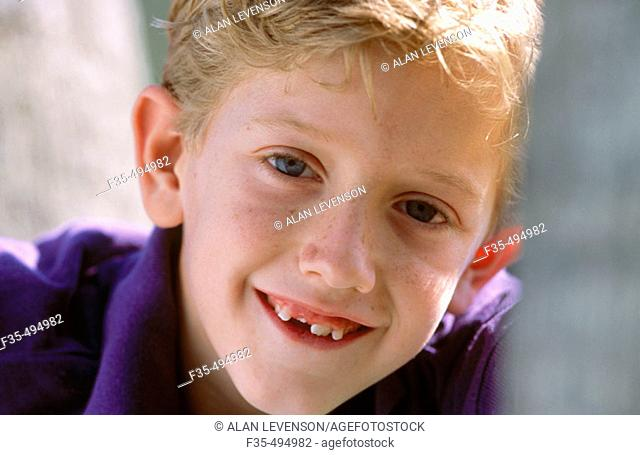 Headshot of Blond boy with lost tooth