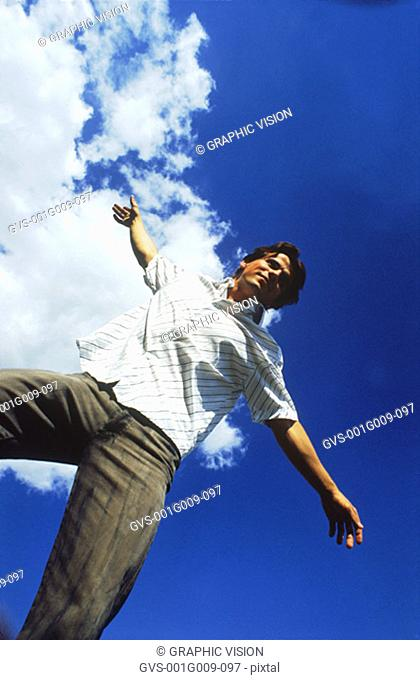 Young man standing with arms outstretched