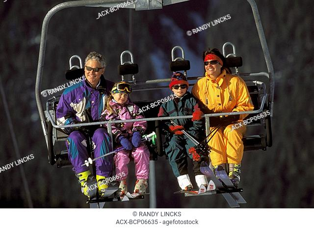 Family on chair lift while skiing at Blackomb, Whistler, British Columbia, Canada