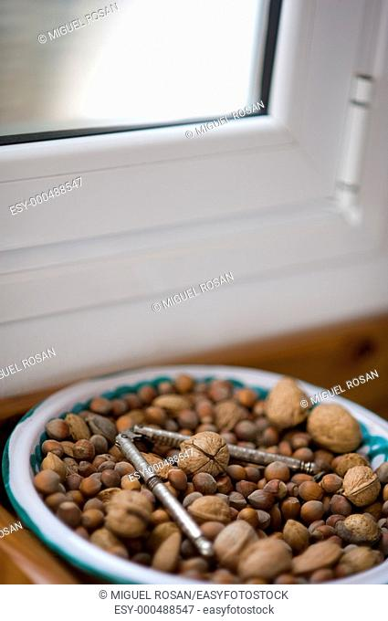 Ceramic plate decorated with nuts, by the window