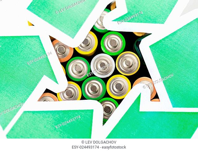 waste recycling, garbage disposal, environment and ecology concept - close up of used alkaline batteries and green recycling symbol