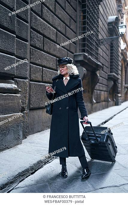 Mature businesswoman wearing black coat and leather cap on busines trip looking at mobile phone