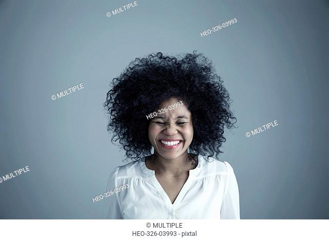 Portrait enthusiastic mixed race young woman with curly black afro hair laughing with eyes closed