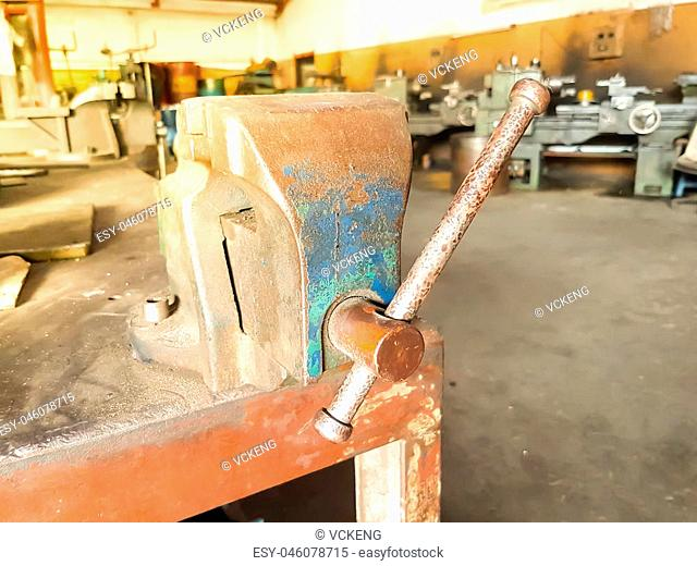 old Bench Vise hand tool with rust on table in factory