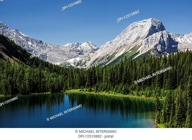 Colourful alpine lake surrounded by mountains and blue sky, Spray Lake Provincial Park; Kananaskis Country, Alberta, Canada