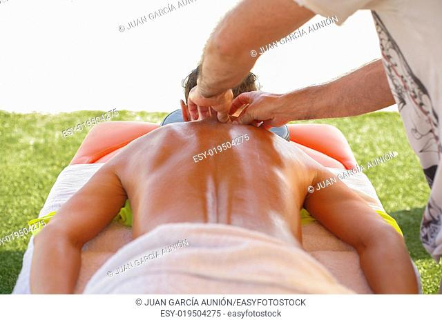 Massage therapist working with suntanned beautiful woman at beach resort