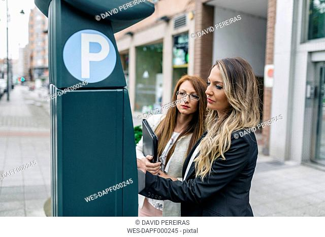 Two businesswomen at pay and display ticket machine in the city
