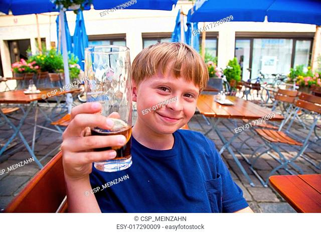 happy smiling child toastes with pleasure with non alcoholic drinks