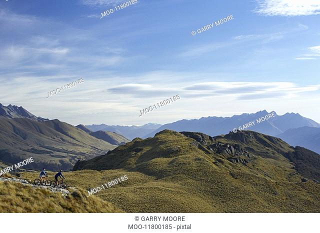 Two cyclists riding in hills back view