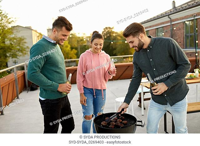 happy friends having bbq party on rooftop