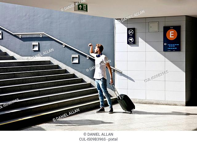 Young man with wheeled trolley bag, in front of steps in train station
