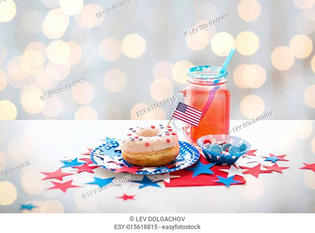 american independence day, celebration, patriotism and holidays concept - close up of glazed sweet donut with flag and candies in disposable tableware at 4th...
